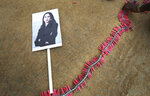 A portrait of U.S. Vice President-elect Kamala Harris lies on the ground as a villager prepares to burst firecrackers ahead of Harris' inauguration, in Thulasendrapuram, the hometown of Harris' maternal grandfather, south of Chennai, Tamil Nadu state, India, Wednesday, Jan. 20, 2021. A tiny, lush-green Indian village surrounded by rice paddy fields was beaming with joy Wednesday hours before its descendant, Kamala Harris, takes her oath of office and becomes the U.S. vice president. (AP Photo/Aijaz Rahi)