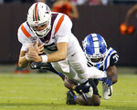 Virginia Tech quarterback Ryan Willis (5) is tackled from behind by Duke defender Josh Blackwell (31) in the first half of an NCAA college football game, Friday, Sept. 27, 2019, in Blacksburg, Va. (Matt Gentry/The Roanoke Times via AP)