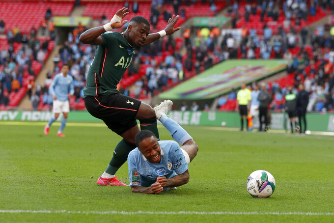 Tottenham's Serge Aurier fouls Manchester City's Raheem Sterling, on the ground, during the English League Cup final soccer match between Manchester City and Tottenham Hotspur at Wembley stadium in London, Sunday, April 25, 2021. (AP Photo/Alastair Grant)