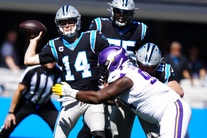 Minnesota Vikings defensive tackle Dalvin Tomlinson (94) chases Carolina Panthers quarterback Sam Darnold (14) during the first half of an NFL football game, Sunday, Oct. 17, 2021, in Charlotte, N.C. (AP Photo/Jacob Kupferman)