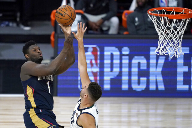 New Orleans Pelicans' Zion Williamson, left, shoots over Utah Jazz's Georges Niang during the first half of an NBA basketball game Thursday, July 30, 2020, in Lake Buena Vista, Fla. (AP Photo/Ashley Landis, Pool)