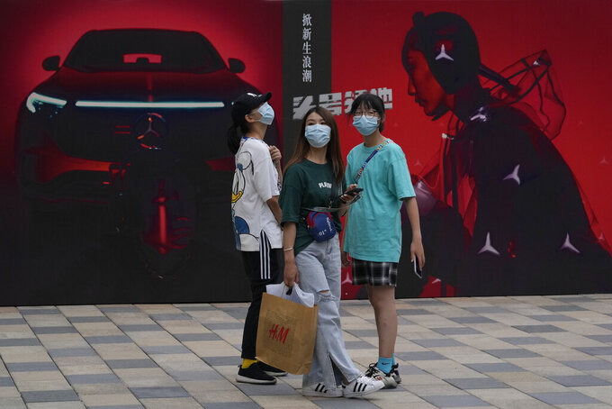 Shoppers past near advertisements for Mercedes Benz at a mall in Beijing on Thursday, July 8, 2021. China's auto sales rose 27% in the first half of 2021 from a year earlier but still were below pre-pandemic levels, and production and sales fell in June due to global shortages of processor chips, an industry group reported Friday. (AP Photo/Ng Han Guan)