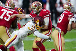 San Francisco 49ers quarterback Nick Mullens (4) takes a hit after the throw by Washington Football Team strong safety Kamren Curl (31) during the first half of an NFL football game, Sunday, Dec. 13, 2020, in Glendale, Ariz. (AP Photo/Ross D. Franklin)
