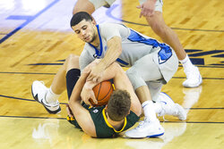 North Dakota State's Rocky Kreuser, bottom, and Creighton's Marcus Zegarowski, top, fight over the ball during the second half of an NCAA college basketball game in Omaha, Neb., Sunday, Nov. 29, 2020. (AP Photo/Kayla Wolf)