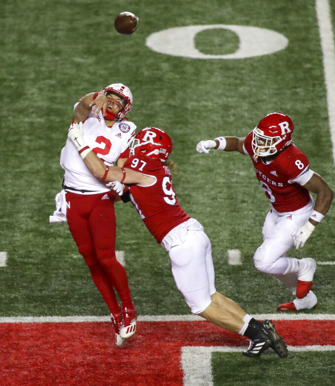 Nebraska quarterback Adrian Martinez (2) is hit by Rutgers defensive lineman Mike Tverdov (97) as he throws the ball during the second quarter of an NCAA college football game Friday, Dec. 18, 2020, in Piscataway, N.J. Martinez was penalized for intentional grounding on this play. (Andrew Mills/NJ Advance Media via AP)