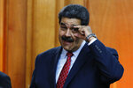 Venezuelan President Nicolas Maduro gestures to military leaders to keep their eyes open, at the end of a press conference inside the presidential palace in Caracas, Venezuela, Friday, Jan. 25, 2019, amid a political power struggle with an opposition leader who declared himself interim president. (AP Photo/Ariana Cubillos)