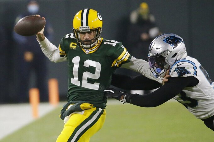 Green Bay Packers' Aaron Rodgers tries to run past Carolina Panthers' Brian Burns during the first half of an NFL football game Saturday, Dec. 19, 2020, in Green Bay, Wis. (AP Photo/Mike Roemer)