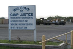 In this photo reviewed by U.S. military officials, a sign welcomes people to Camp Justice, Sunday, Aug. 29, 2021, in Guantanamo Bay Naval Base, Cuba. Camp Justice is where the military commission proceedings are held for detainees charged with war crimes. (AP Photo/Alex Brandon)