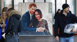 People walk past a picture of Britain's Prince Harry and Meghan Duchess of Sussex, in Windsor, Friday, Jan. 10, 2020. Britain's Prince Harry and his wife, Meghan, said they are planning