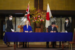 British International Trade SecretaryLiz Truss, center left, signs a document with Japanese Foreign Minister Toshimitsu Motegi, center right, for economic partnership between Japan and Britain at Iikura Annex of the Foreign Ministry in Tokyo Friday, Oct. 23, 2020. Japan and Britain signed a bilateral free trade deal Friday in the the first such major post-Brexit deal, reducing tariffs on Yorkshire lamb sold in Japan, as well as auto parts for Japan's Nissan plant. (Kimimasa Mayama/Pool Photo via AP)