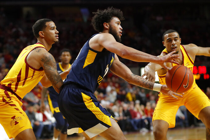 West Virginia guard Jermaine Haley, center, passes the ball between Iowa State defenders, Nick Weiler-Babb, left, and Talen Horton-Tucker, right, during the first half of an NCAA college basketball game, Wednesday, Jan. 30, 2019, in Ames, Iowa. (AP Photo/Charlie Neibergall)