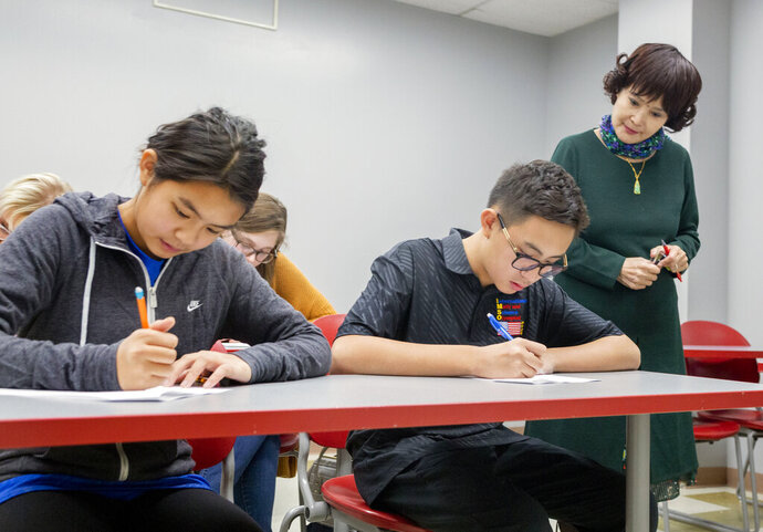 The youngest students to ever attend UNLV Shenmei Wu, 13, left, and Shenlone Wu, 12, center, and professor Xiaoling Hays focus during a Chinese final exam at UNLV in Las Vegas on Monday, Dec. 9, 2019.(Bizuayehu Tesfaye/Las Vegas Review-Journal via AP)