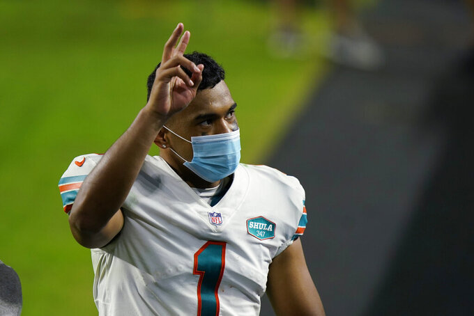 FILE - Miami Dolphins quarterback Tua Tagovailoa (1) gesture as he leaves the field at the end of an NFL football game against the Los Angeles Chargers in Miami Gardens, Fla., in this Sunday, Nov. 15, 2020, file photo. The Dolphins defeated the Chargers 29-21. The Dolphins play the New England Patriots on Sunday. (AP Photo/Lynne Sladky, File)