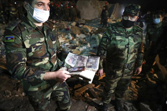 An Azerbaijan's officer shows a family pictures to journalists as soldiers and firefighters search for survivors in a residential area that was hit by rocket fire overnight by Armenian forces, early Saturday, Oct. 17, 2020, in Gyanga,  Azerbaijan's second largest city, near the border with Armenia. (AP Photo/Aziz Karimov)