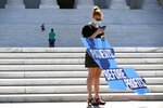 A child runs down the steps of the Supreme Court on Capitol Hill in Washington, Monday, June 29, 2020, as an anti-abortion protester holds a sign after the court struck down a Louisiana law regulating abortion clinics.  The Supreme Court has struck down a Louisiana law regulating abortion clinics, reasserting a commitment to abortion rights over fierce opposition from dissenting conservative justices in the first big abortion case of the Trump era.  (AP Photo/Patrick Semansky)