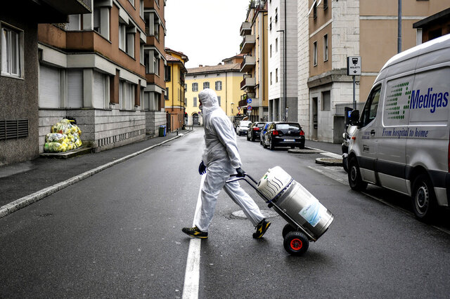 A staffer delivers a medical oxygen tank to coronavirus patients who are being treated at home, in Bergamo, one of the areas worst affected by the virus, Northern Italy, Tuesday, March 31, 2020. The new coronavirus causes mild or moderate symptoms for most people, but for some, especially older adults and people with existing health problems, it can cause more severe illness or death. (Claudio Furlan/LaPresse via AP)