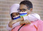 """Alaya Littlejohn hugs her mother, Katra Littlejohn, as they wait in line outside the Duval County Health Department to get a COVID-18 test in Jacksonville, Fla., on Wednesday, July 28, 2021. According to Katra, they have both gotten vaccinated against the COVID-19 virus but wanted to get tested """"Just to be safe"""". As the number of people infected by the COVID-19 virus spikes, the Duval County Health Department in Jacksonville's Springfield neighborhood has stayed busy with long lines of residents waiting for cover tests and getting covid vaccines. (Bob Self/The Florida Times-Union via AP)"""