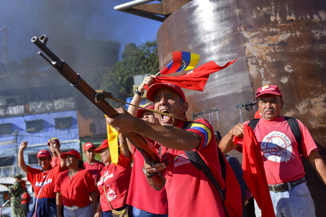 A member of the Bolivarian National Militia brandishes a rifle during an invasion drill in Caracas, Venezuela, Saturday, Feb. 15, 2020. Venezuela's President Nicolas Maduro ordered two days of nationwide military exercises, including participation of civilian militias. (AP Photo/Matias Delacroix)