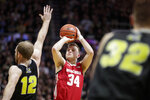 Wisconsin guard Brad Davison (34) shoots over Purdue forward Evan Boudreaux (12) during the first half of an NCAA college basketball game in West Lafayette, Ind., Friday, Jan. 24, 2020. (AP Photo/Michael Conroy)