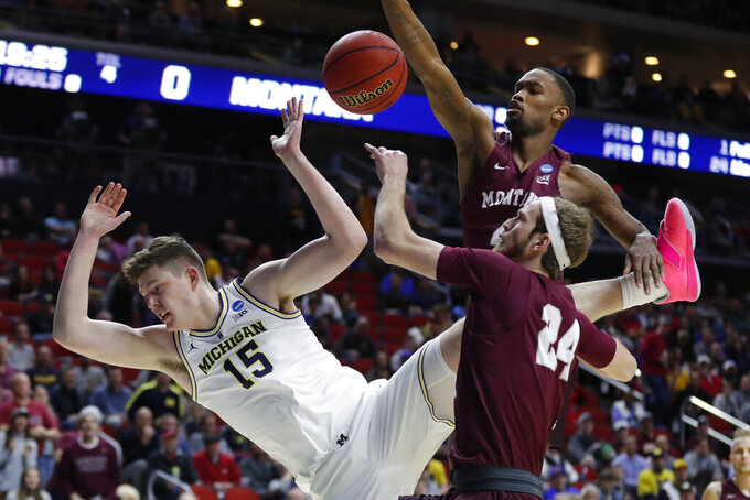 Michigan center Jon Teske (15) is fouled while driving to the basket in front of Montana guard Bobby Moorehead (24) and Sayeed Pridgett, rear, during a first round men's college basketball game in the NCAA Tournament, Thursday, March 21, 2019, in Des Moines, Iowa. (AP Photo/Charlie Neibergall)