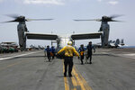 CORRECTS DATE -  In this Friday, May 17, 2019, photo, released by the U.S. Navy, sailors work around an MV-22 Osprey as it lands on the flight deck of the Nimitz-class aircraft carrier USS Abraham Lincoln in the Arabian Sea. Commercial airliners flying over the Persian Gulf risk being targeted by