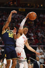 Maryland guard Anthony Cowan Jr. (1) grabs the ball away next to Michigan guard Eli Brooks (55) during the first half of an NCAA college basketball game, Sunday, March 8, 2020, in College Park, Md. (AP Photo/Nick Wass)
