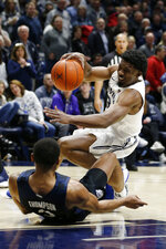 Xavier guard Quentin Goodin, top, collides with Butler guard Aaron Thompson during the first half of an NCAA college basketball game Saturday, March 7, 2020, in Cincinnati. (AP Photo/Gary Landers)