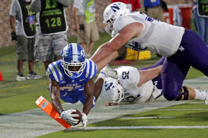 Duke cornerback Josh Blackwell (31) dives into the end zone past Northwestern offensive lineman Ben Wrather (71) and offensive lineman Sam Gerak (52) after he intercepted a pass and ran it in during the second half of an NCAA college football game in Durham, N.C., Saturday, Sept. 18, 2021. The play was called back on a penalty. (AP Photo/Chris Seward)