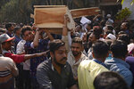 Bangladeshis carry coffins of relatives out from a morgue after they were killed in a fire in Dhaka, Bangladesh, Thursday, Feb. 21, 2019. A devastating fire raced through at least five buildings in an old part of Bangladesh's capital and killed scores of people. (AP Photo/Mahmud Hossain Opu )