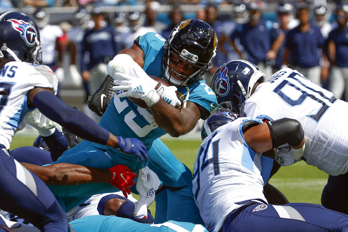 Jacksonville Jaguars running back James Robinson dives over the Tennessee Titans defense including defensive end Amani Bledsoe (94) and defensive tackle Naquan Jones (90) for a 1-yard touchdown during the first half of an NFL football game, Sunday, Oct. 10, 2021, in Jacksonville, Fla. (AP Photo/Stephen B. Morton)
