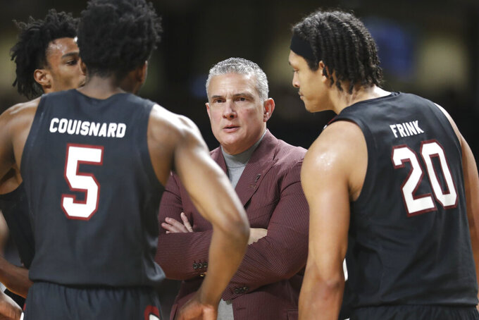 FILE - In this March 7, 2020, file photo, South Carolina head coach Frank Martin talks to Jermaine Couisnard (5) and Alanzo Frink (20) in the second half of an NCAA college basketball game against Vanderbilt in Nashville, Tenn. South Carolina coach Frank Martin carries a new perspective into this season with the Gamecocks. Martin caught COVID-19 during the spring when fear of the disease was spiking and few people knew how to deal with it. But Martin's time in isolation and recovery led to a deeper appreciation of when he and his players would return to the court. (AP Photo/Mark Humphrey, File)