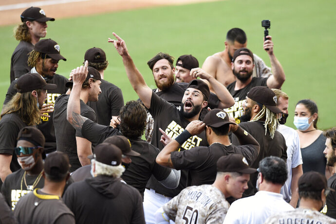 San Diego Padres shortstop Eric Hosmer, center, celebrates after the Padres beat the Seattle Mariners in a baseball game Sunday, Sept. 20, 2020, in San Diego. The Padres clinched a spot in the playoffs. (AP Photo/Denis Poroy)