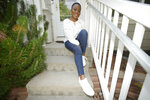 Fashion blogger Abena Antwiwaa poses at her home in Aurora, Colo., on Friday, Aug. 6, 2021. Antwiwaa is one of dozens of influencers, ranging from busy moms and fashion bloggers to African refugee advocates and religious leaders, getting paid by the state to post vaccine information on a local level in hopes of stunting a troubling summer surge of COVID-19.  (AP Photo/David Zalubowski)