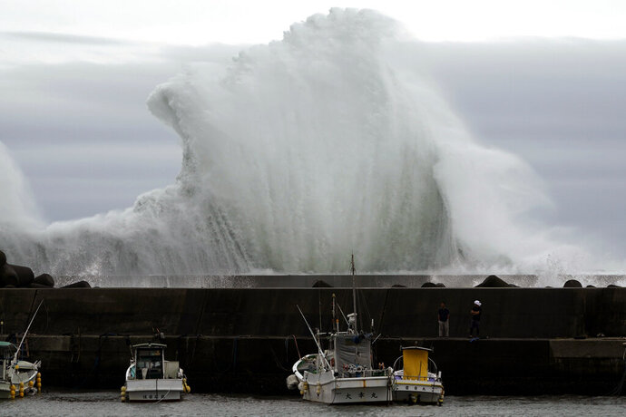 Men look at fishing boats as surging waves hit against the breakwater while Typhoon Hagibis approaches at a port in town of Kiho, Mie Prefecture, Japan Friday, Oct. 11, 2019. A powerful typhoon is advancing toward the Tokyo area, where torrential rains are expected this weekend. (AP Photo/Toru Hanai)