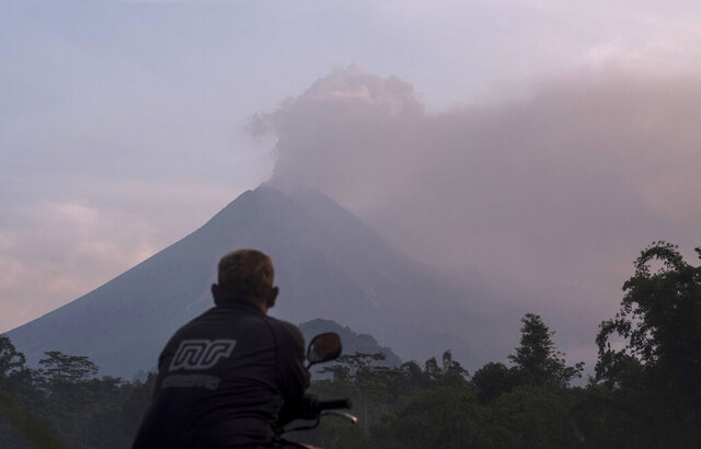 A man watches as Mount Merapi spews volcanic material into the air in Sleman, Indonesia, Tuesday, March 3, 2020. Indonesia's most active volcano erupted Tuesday, spewing sand and pyroclastic material and sending massive smoke-and-ash column into the sky. (AP Photo/Slamet Riyadi)