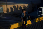 Refugees and migrants are silhouetted on a wall as they arrive at the port of Lavrio, about 75 kilometers (48miles) south of Athens, Tuesday, Sept. 29, 2020. Greek authorities have moved nearly 1,000 asylum-seekers from eastern Aegean islands to the mainland as part of efforts to improve conditions in overcrowded island camps. Most of the people on a ferry that docked Tuesday at Lavrio, near Athens, were from a temporary facility hastily built on the island of Lesbos to replace a squalid camp that angry residents burned down three weeks ago. (AP Photo/Petros Giannakouris)
