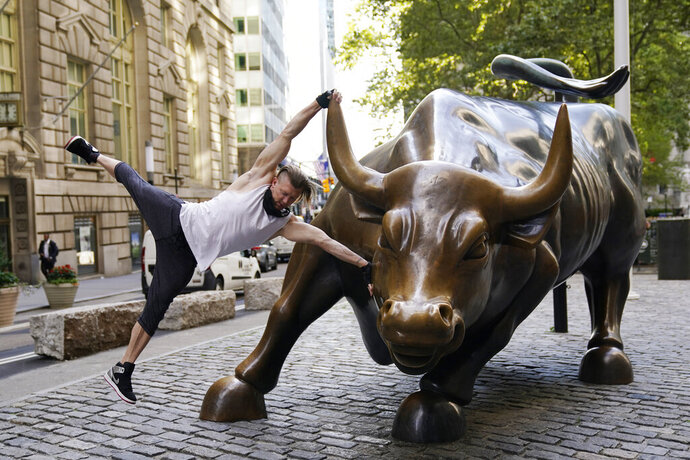 Stuart McKenzie, of London, takes a swing on the Charging Bull statue in New York's financial district, Tuesday, Sept. 8, 2020. More sharp declines for big tech stocks are dragging Wall Street toward a third straight loss on Tuesday. (AP Photo/Mark Lennihan)