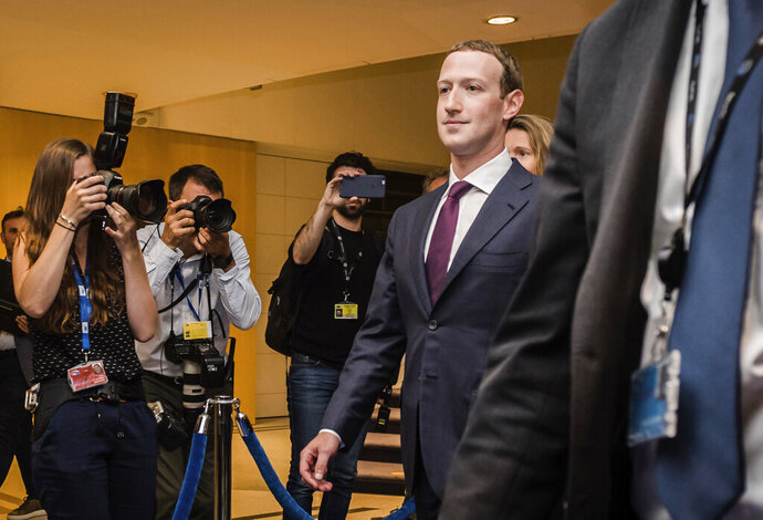 FILE - In this file photo dated Tuesday, May 22, 2018, Facebook CEO Mark Zuckerberg leaves the EU Parliament in Brussels during a series of meetings over data protection standards at the internet giant and alleged misuse of the personal information. The European Federal Cartel Office issued a ruling in February 2019 making it harder for Facebook to combine data from all its services to target ads more precisely to users. (AP Photo/Geert Vanden Wijngaert, FILE)