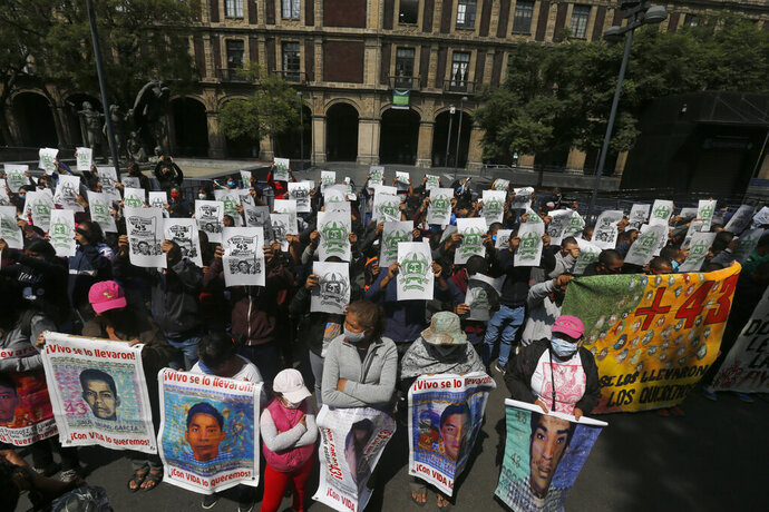 Students, joined by relatives of the 43 missing students from the Rural Normal School of Ayotzinapa, stand outside the Supreme Court during a protest to mark the upcoming sixth anniversary of the students' disappearance, in Mexico City, Wednesday, Sept. 23, 2020. Family members continue to call for justice six years after the Ayotzinapa students were allegedly taken from buses by local police and turned over to a drug gang.(AP Photo/Marco Ugarte)