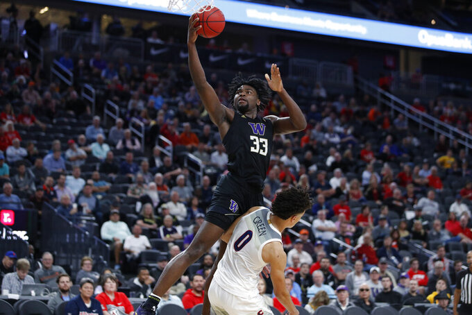 Washington's Isaiah Stewart (33) fouls Arizona's Josh Green (0) during the first half of an NCAA college basketball game in the first round of the Pac-12 men's tournament Wednesday, March 11, 2020, in Las Vegas. (AP Photo/John Locher)