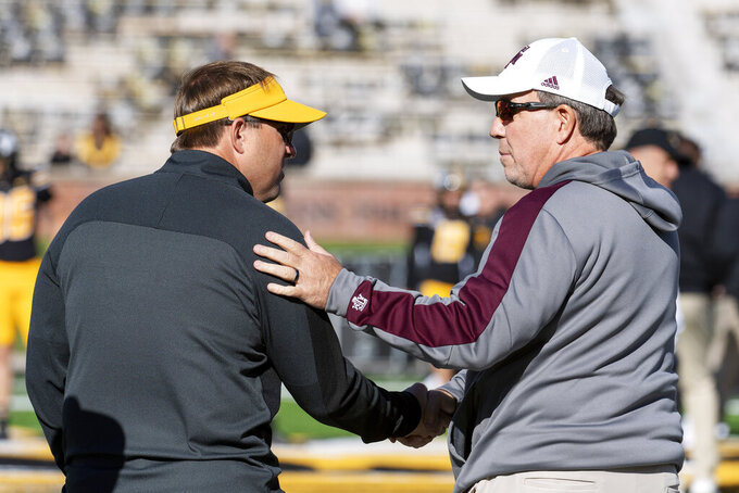 Missouri head coach Eliah Drinkwitz, left, and Texas A&M head coach Jimbo Fisher, right, talk on the field before the start of an NCAA college football game Saturday, Oct. 16, 2021, in Columbia, Mo. (AP Photo/L.G. Patterson)