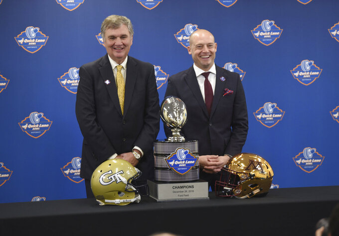 FILE  -  In this Dec. 5, 2018 file photo Georgia Tech head coach Paul Johnson, left, and University of Minnesota head coach P.J. Fleck pose with the NCAA college football Quick Lane Bowl trophy at a news conference in Allen Park, Mich. Johnson will lead Georgia Tech for the final time Wednesday, Dec. 26, 2018 against Minnesota in the Quick Lane Bowl. Johnson is 82-59 at Georgia Tech over 11 seasons and 128-88 overall, including six seasons at Navy. Minnesota has a nation-high 52 percent of its roster filled by freshman. The young became bowl eligible by beating Purdue 41-10 and Wisconsin 37-15 in November. (Max Ortiz/Detroit News via AP)