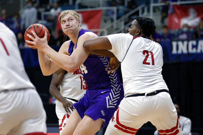 Abilene Christian center Kolton Kohl, left, looks for a shot around Nicholls State center Ryghe Lyons (21) during the first half of an NCAA college basketball game for the Southland Conference men's tournament championship Saturday, March 13, 2021, in Katy, Texas. (AP Photo/Michael Wyke)