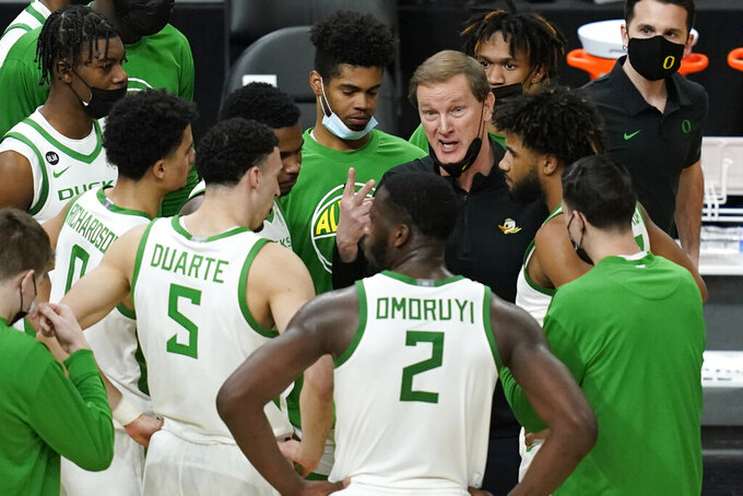 Oregon head coach Dana Altman speaks with players at a timeout during the first half of an NCAA college basketball game against Oregon State in the semifinal round of the Pac-12 men's tournament Friday, March 12, 2021, in Las Vegas. (AP Photo/John Locher)