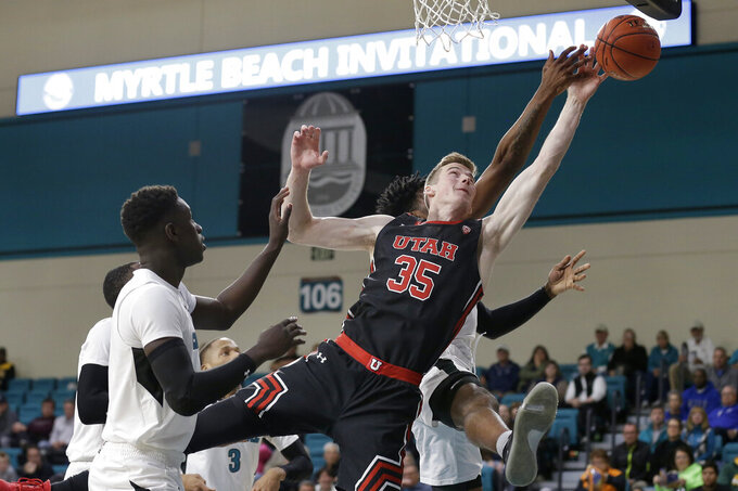 Utah center Branden Carlson (35) drives to the basket against Coastal Carolina guard Ebrima Dibba (0) during the first half of an NCAA college basketball game at the Myrtle Beach Invitational in Conway, S.C., Thursday, Nov. 21, 2019. (AP Photo/Gerry Broome)
