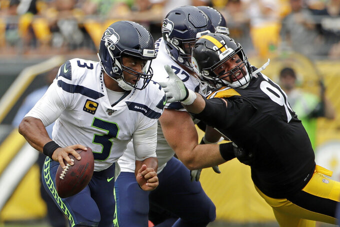 Seattle Seahawks quarterback Russell Wilson (3) scrambles past Pittsburgh Steelers defensive end Cameron Heyward (97), who is blocked by Seahawks offensive guard Ethan Pocic (77) during the second half of an NFL football game in Pittsburgh, Sunday, Sept. 15, 2019. The Seahawks won 28-26. (AP Photo/Gene J. Puskar)