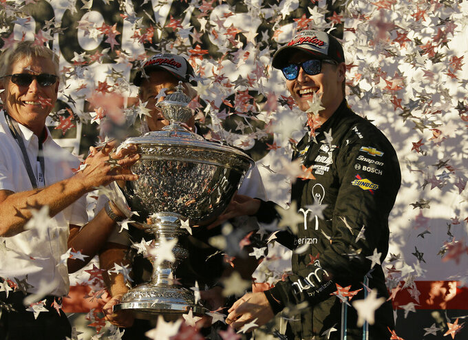 FILE - In this Sept. 17, 2017, file photo, Josef Newgarden, right, stands and celebrates after being presented the Astor Cup for winning the IndyCar championship in Sonoma, Calif. Looking on at center behind the trophy is team owner Roger Penske. Newgarden wouldn't change the career path he has had through eight IndyCar seasons, even though the American driver wanted more success earlier.  (AP Photo/Eric Risberg, File)