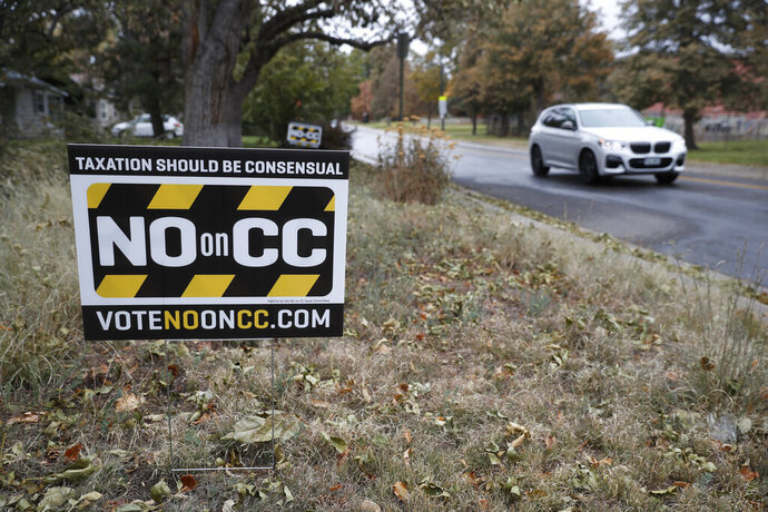 In this Friday, Oct. 18, 2019, photograph, a vehicle passes by a lawn sign calling for voters to cast ballots against a measure to dismantle part of Colorado's state tax laws on election day Tuesday, Nov. 5. Coloradoans will be asked to decide if the state can permanently keep tax revenue that otherwise would be refunded under limits set by a constitutional amendment called the Taxpayer's Bill of Rights, or TABOR. (AP Photo/David Zalubowski)