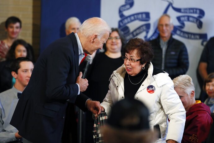 Democratic presidential candidate former Vice President Joe Biden helps an audience member to her chair during a bus tour stop, Tuesday, Dec. 3, 2019, in Mason City, Iowa. (AP Photo/Charlie Neibergall)