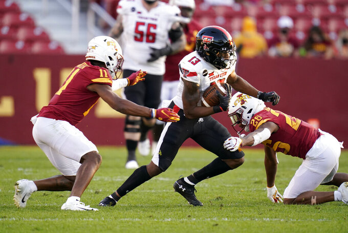 Texas Tech wide receiver Erik Ezukanma (13) runs from Iowa State defensive back Lawrence White IV (11) and defensive back Anthony Johnson Jr. (26) after catching a pass during the second half of an NCAA college football game, Saturday, Oct. 10, 2020, in Ames, Iowa. Iowa State won 31-15. (AP Photo/Charlie Neibergall)